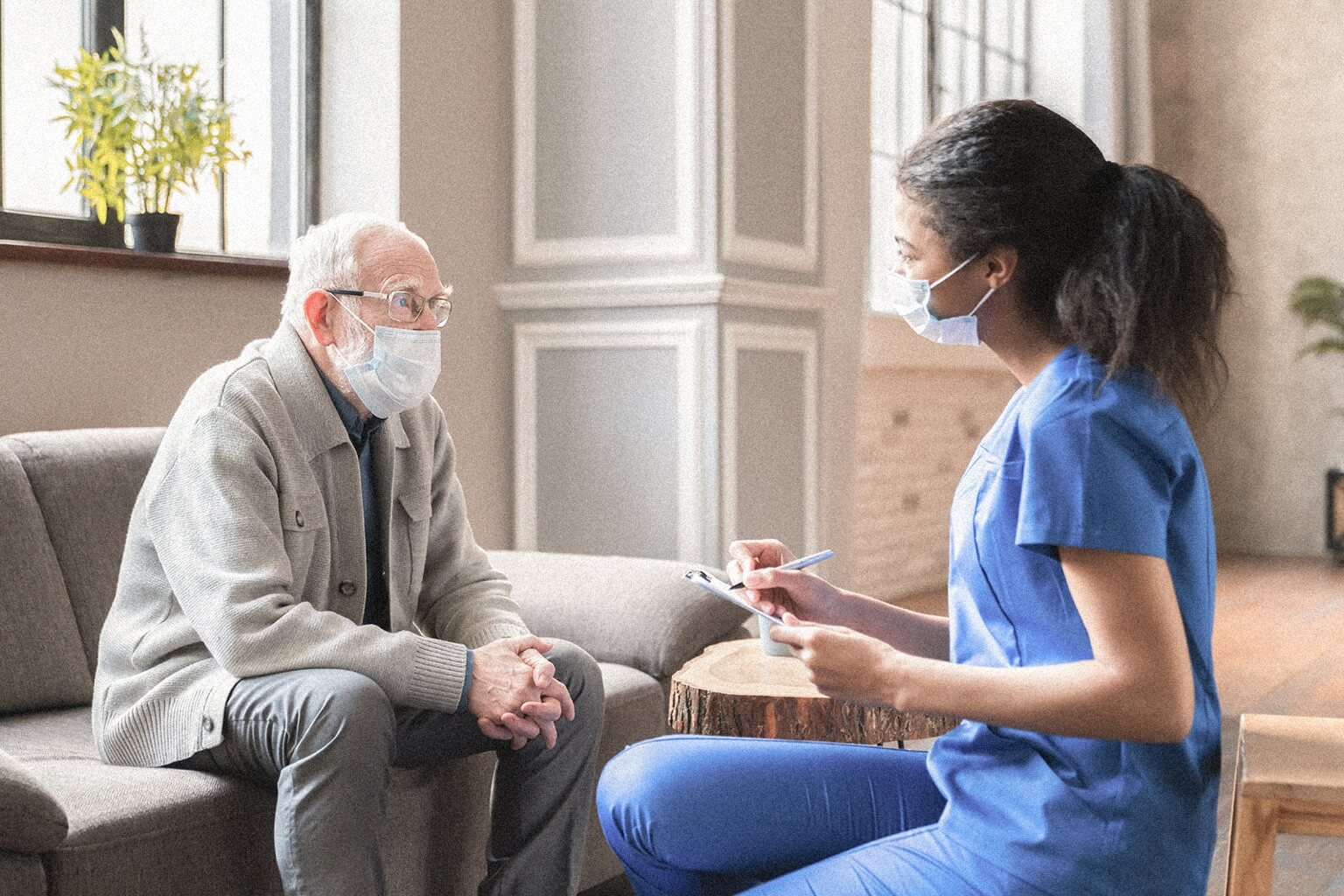 A certified case manager sits and speaks with an older patient. Both are masked.