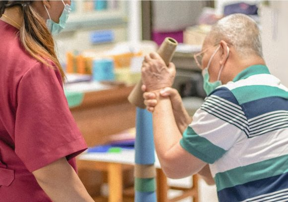 An occupational therapist works with an older patient on grip strength and arm mobility. Both are masked.