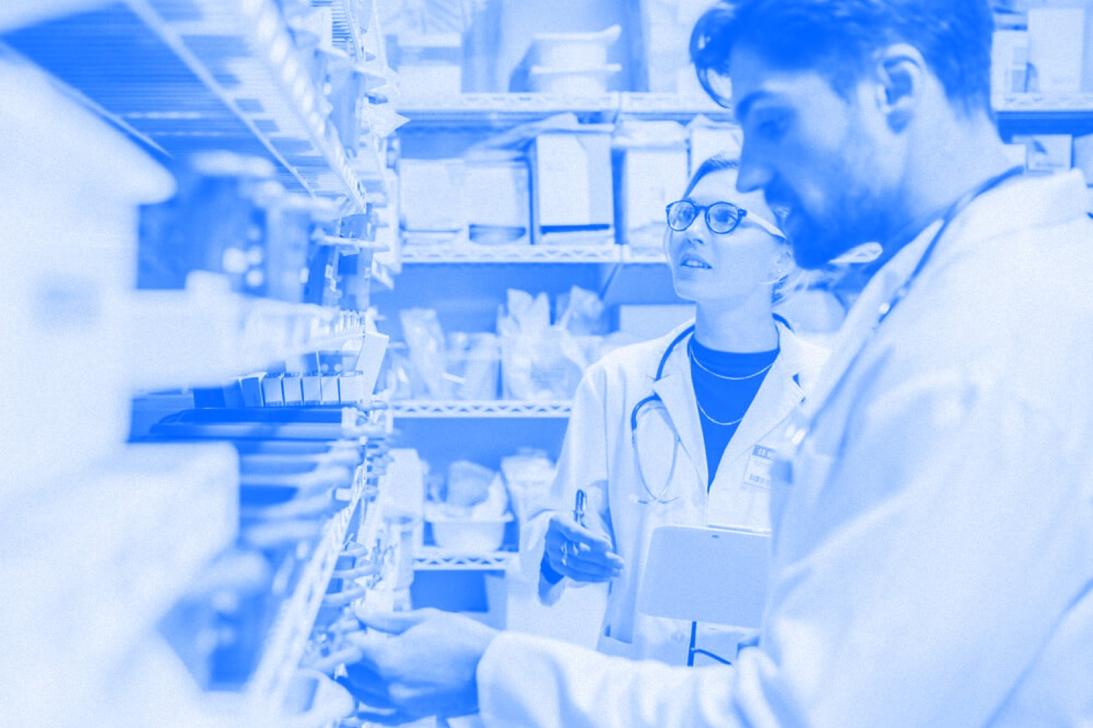 A pharmacy technician and pharmacist work together while looking at shelves of medicine. Blue-tinted photograph.