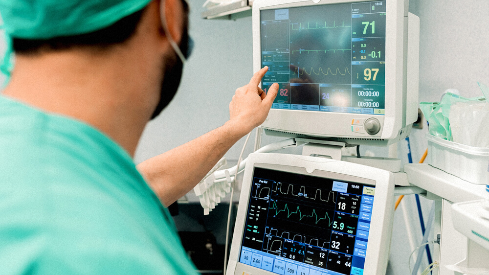 A nurse monitors a patient's vitals from two monitors—pointing at one specific graph.
