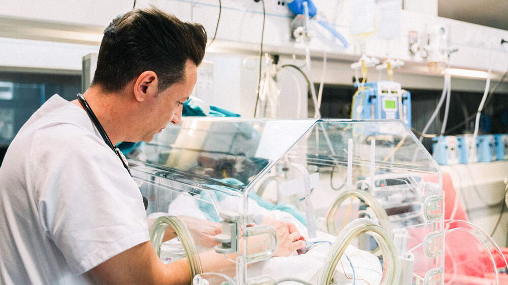 A RN cares for a baby in an incubator.