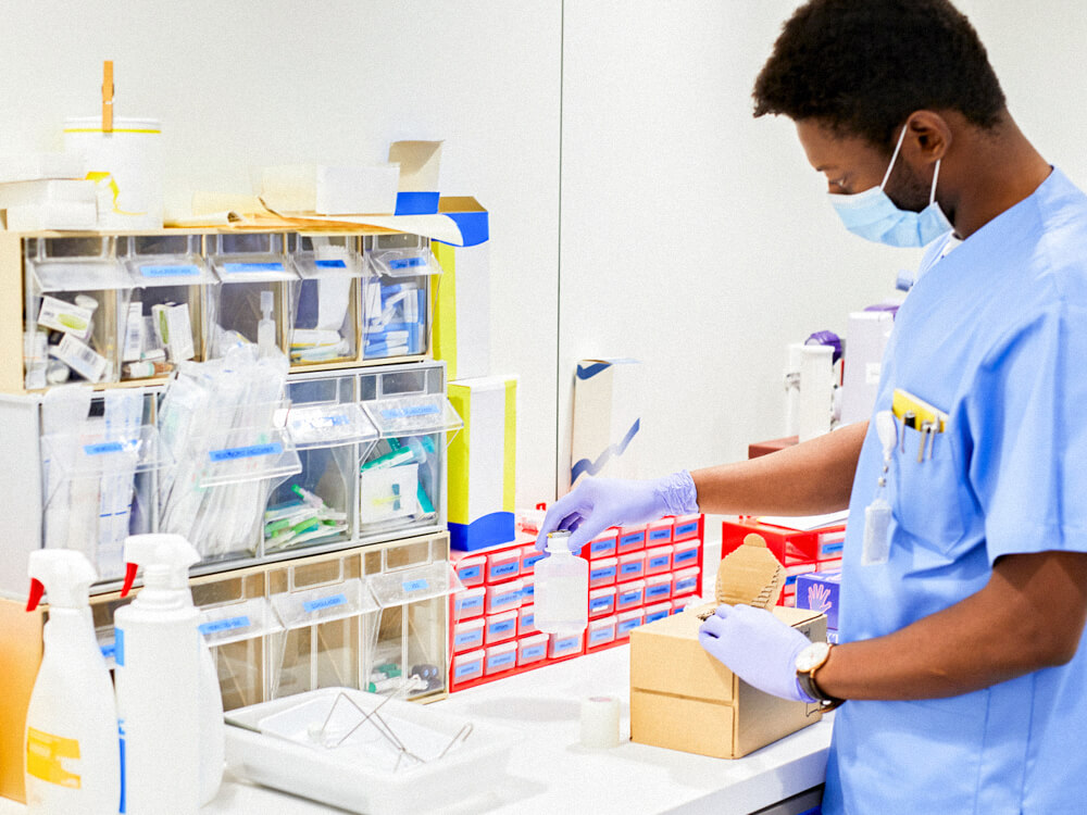 A nurse at a workstation of medical equipment.
