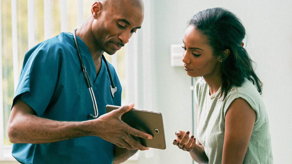 A nurse and patient look together at a tablet in a doctor's office.