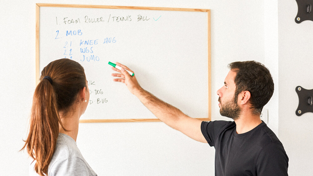 Personal trainer reviews workout written on a whiteboard with a client.