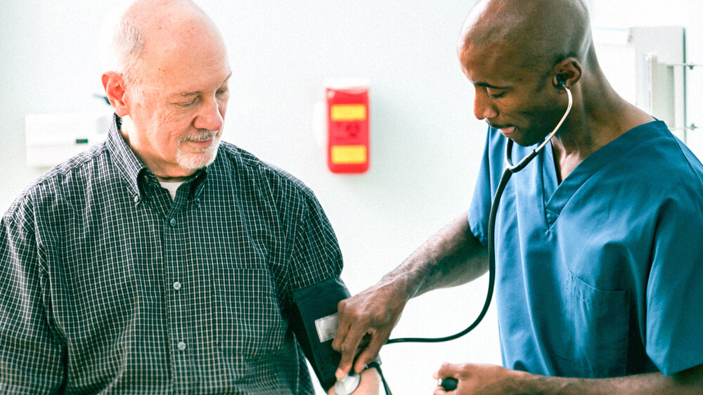 A nurse practitioner takes the blood pressure and listens to the blood flow of a senior patient.