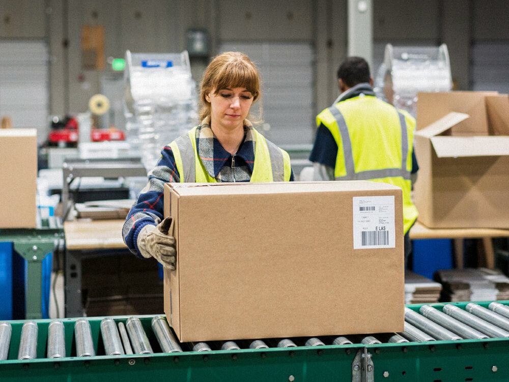 A person inspects a box on an assembly line.