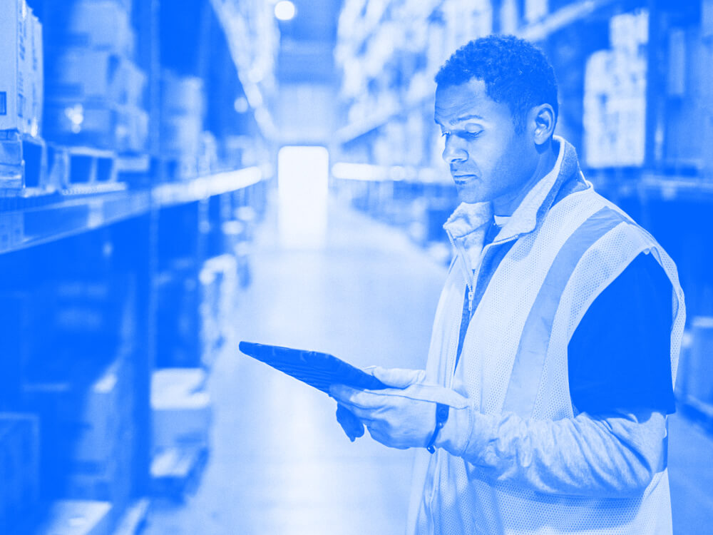 A person holds a tablet in the aisle of a warehouse.