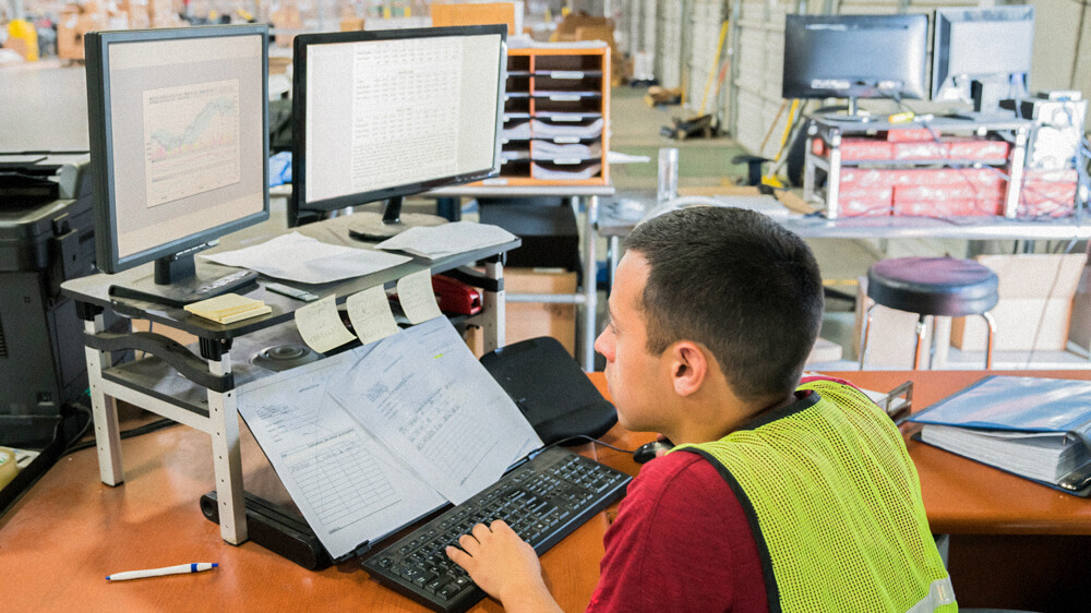 A person wearing a safety vest works at a desk with two monitors, sticky notes, and printouts.
