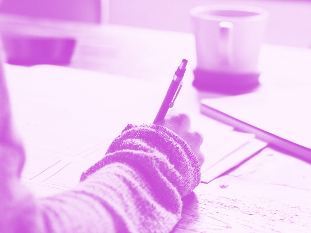 Social worker takes notes while sitting at a desk.