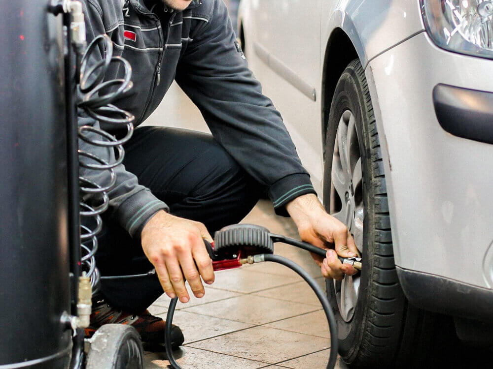 Automotive mechanic adding air in a tire.