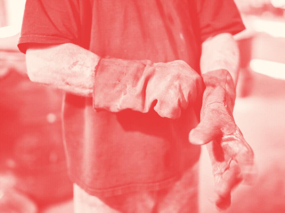 Automotive mechanic pulling on work gloves.