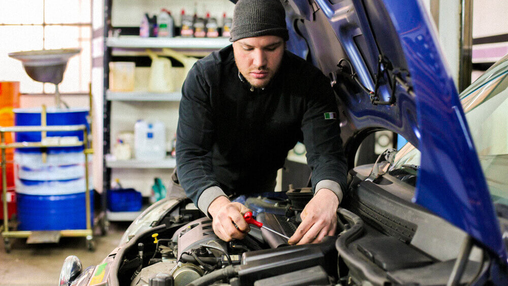 Automotive mechanic working under the hood of a blue vehicle in a shop.