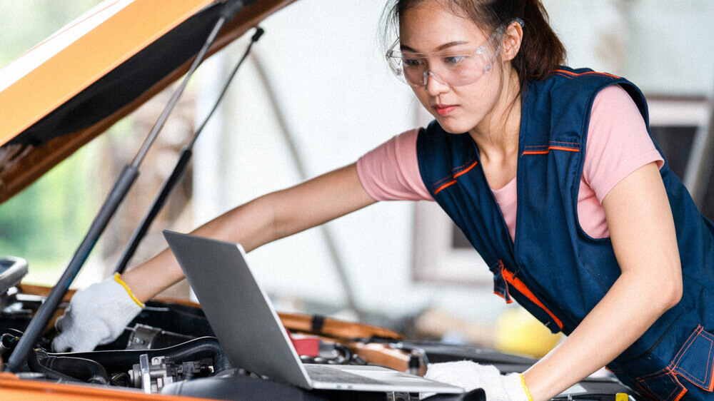 Automotive mechanic adjusting something under the hood while referencing a laptop.