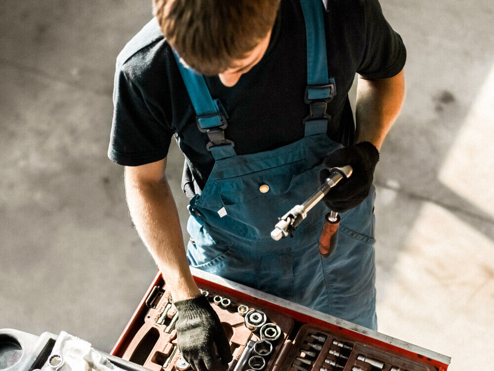 Automotive mechanic pulling sockets from a socket set in drawer.
