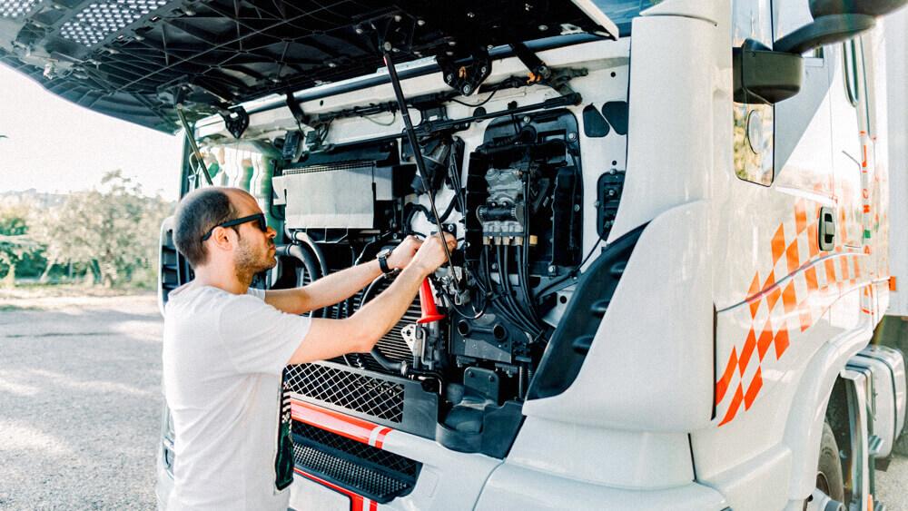 Automotive mechanic working under the hood of a semi truck.