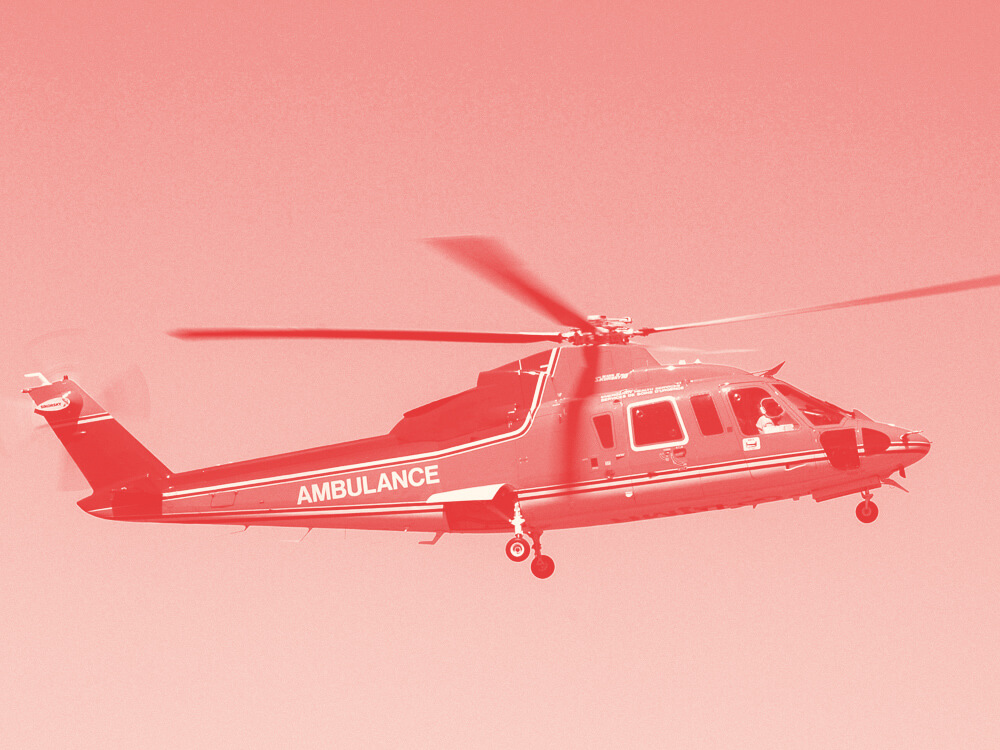 A red medical helicopter flying in a blue sky.