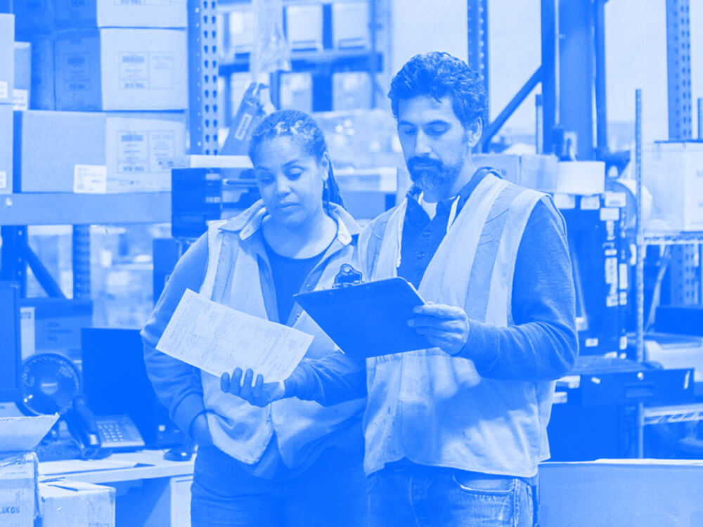 Two employees review a clipboard in a warehouse.