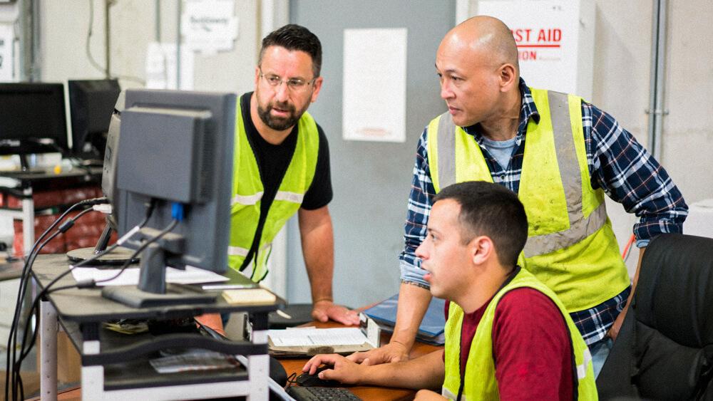 Three safety professionals huddle around a workstation.
