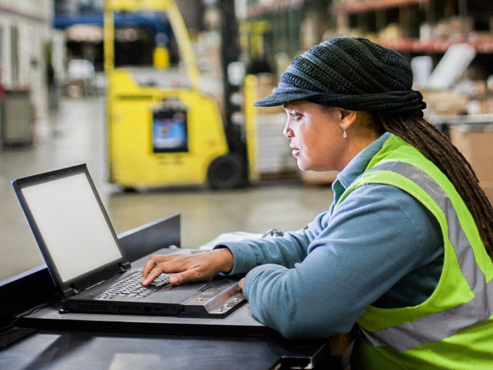 An employee works on a laptop in a warehouse.