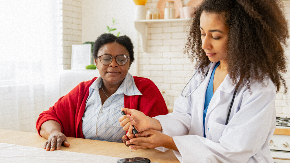 A diabetes care specialist pricks the finger of a patient.