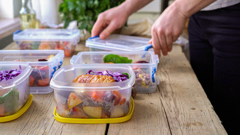 Tupperware containers with prepared and portioned food sit on a table.