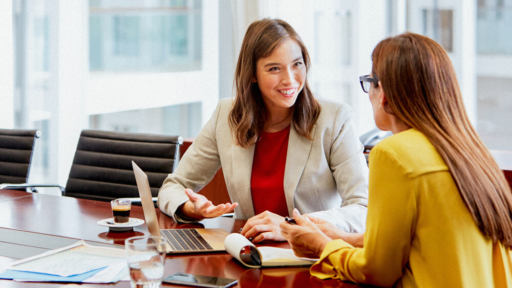 A certified financial planner talks with a client in a corporate office over laptop and notes.
