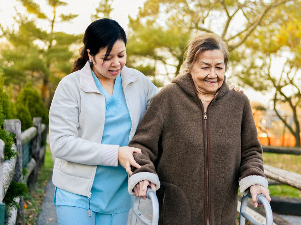 A nursing assistant helps a person walk outside with a walker.
