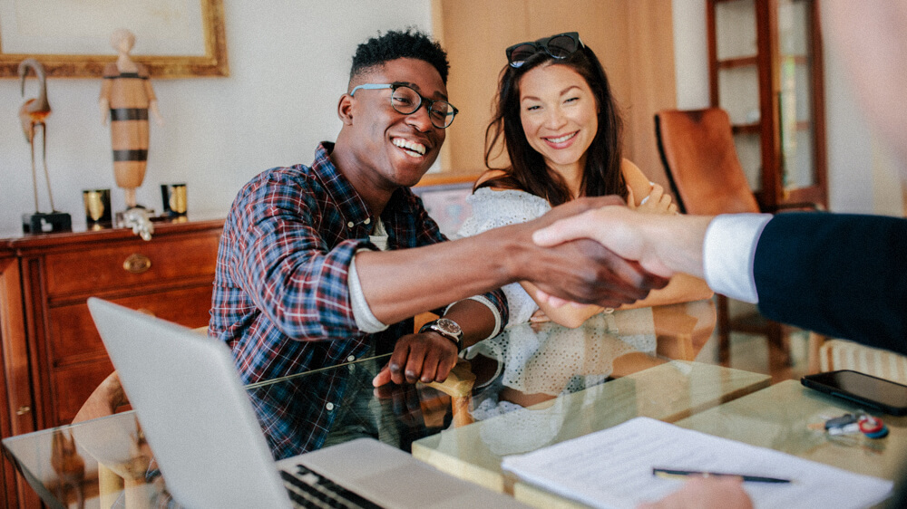 A realtor shakes hands with a couple from across their desk.