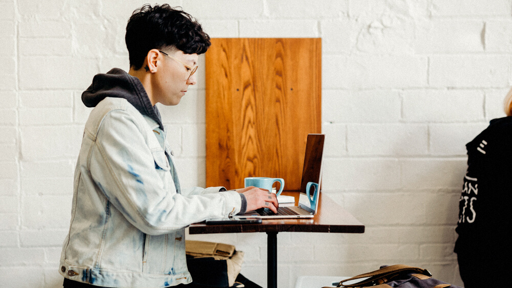 Computer technician wearing a jean jacket and hoodie works on a laptop.