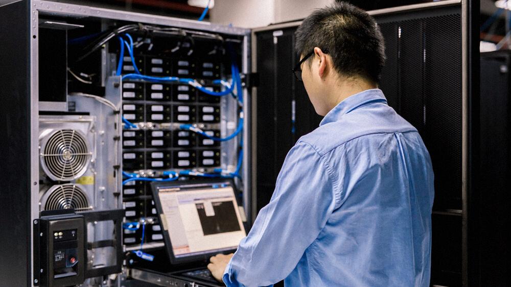 IT professional troubleshoots server rack.
