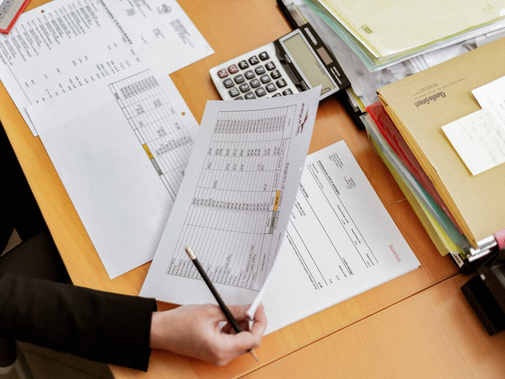 Financial general securities representative reviews printed documents on their desk.