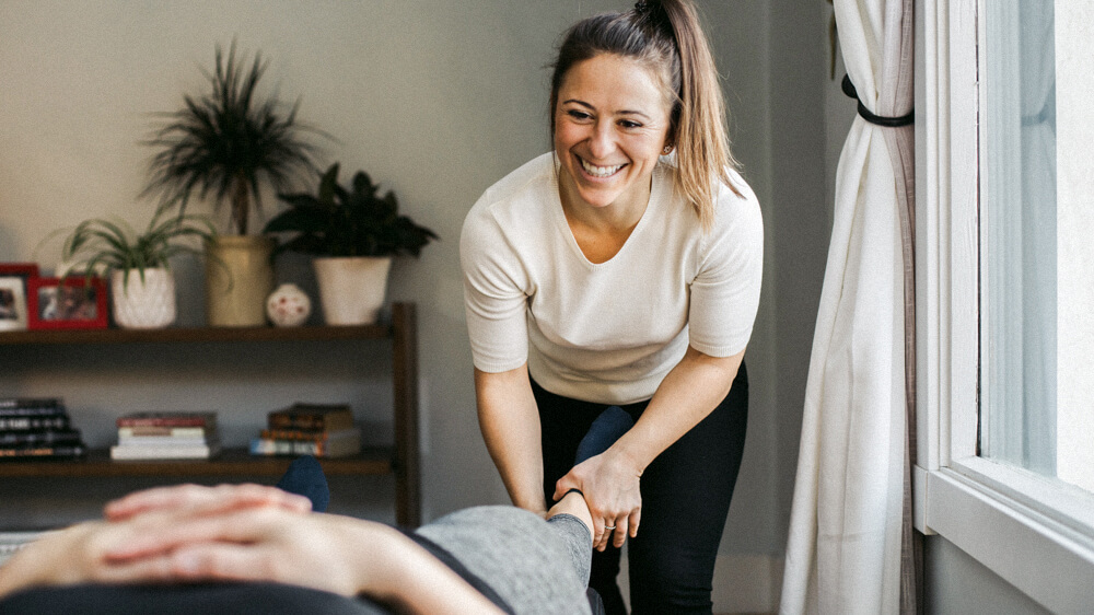 A physical therapist assistant massages the lower leg of a patient.