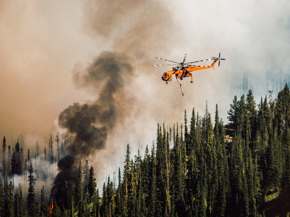 An orange emergency helicopter helps fight a forest fire.