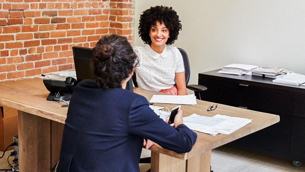 An HR professional meets with an employee in their office.