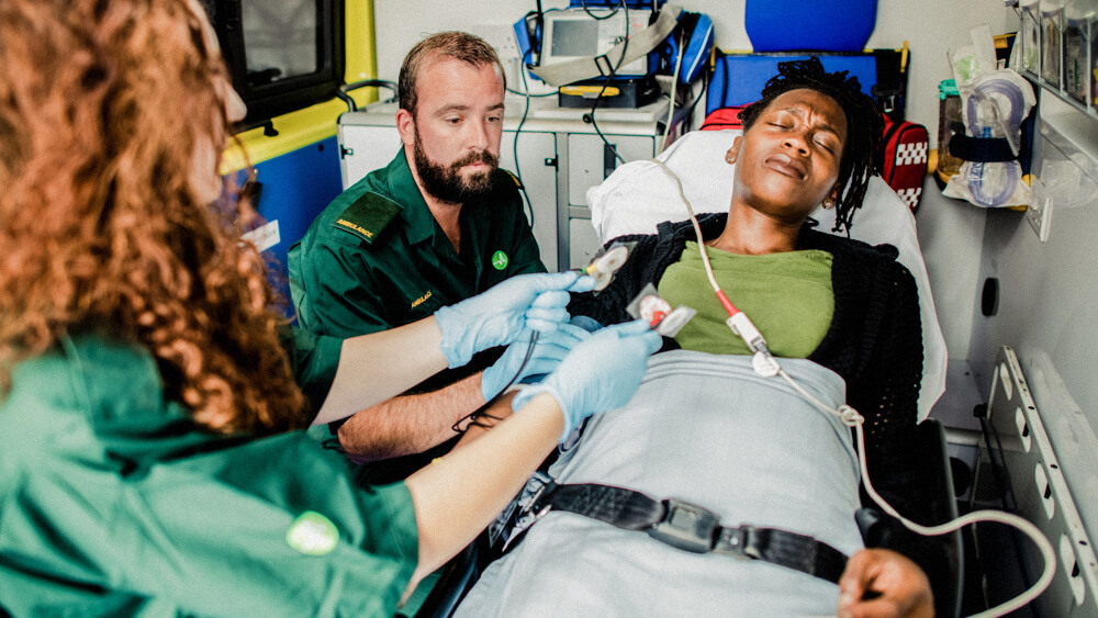 Two paramedics care for a patient inside an ambulance.