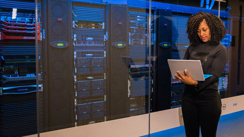 Information security manager stands in front of servers while monitoring from a laptop.