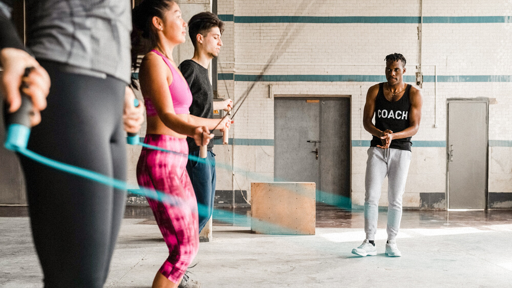 Personal trainer observes a group of people jumping rope in a gym.
