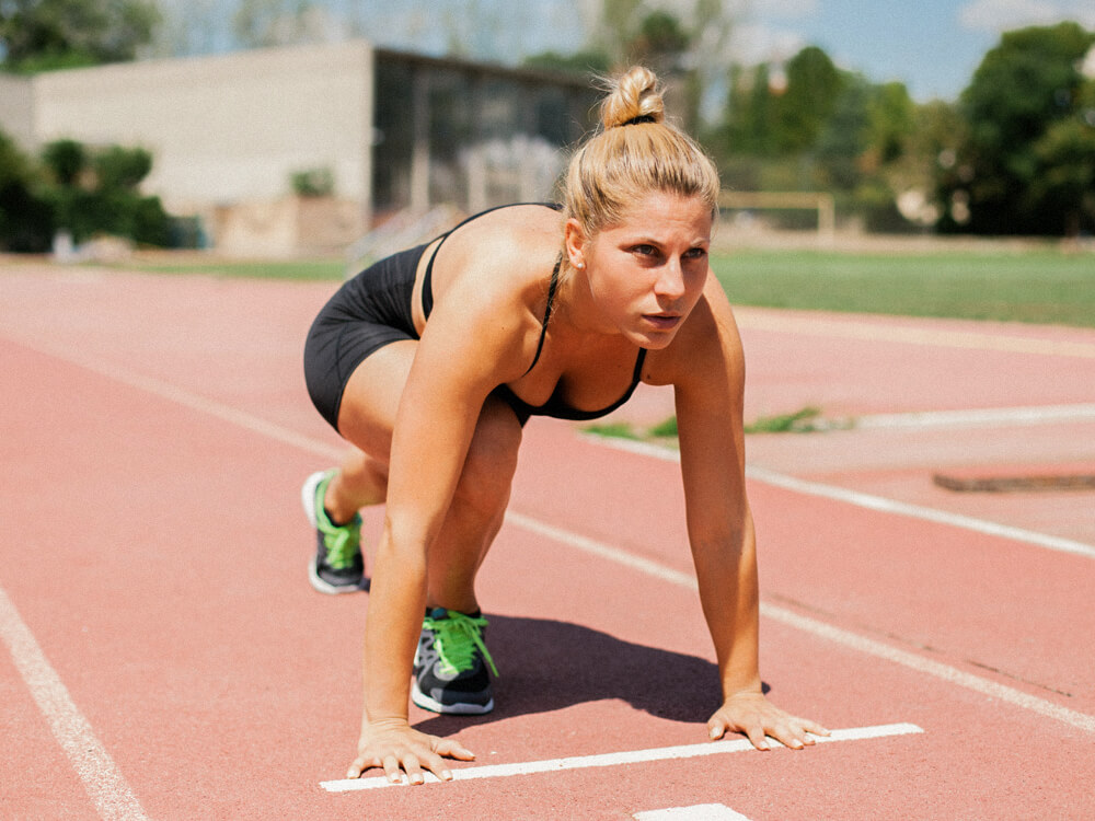 A sprinter on track in a lunge set position.