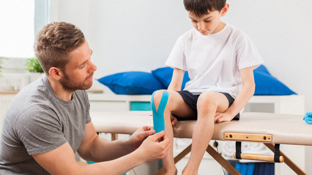 An occupational therapist assistant applies medical tape around a child's knee.