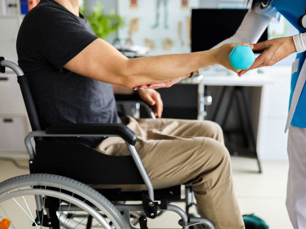 An occupational therapist does exercises with a patient in a wheelchair.