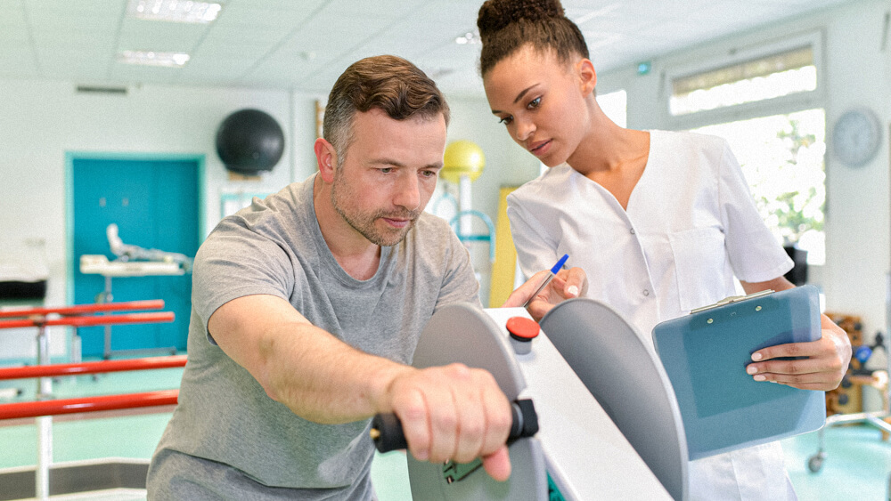 An occupational therapist works with a patient on arm strength.