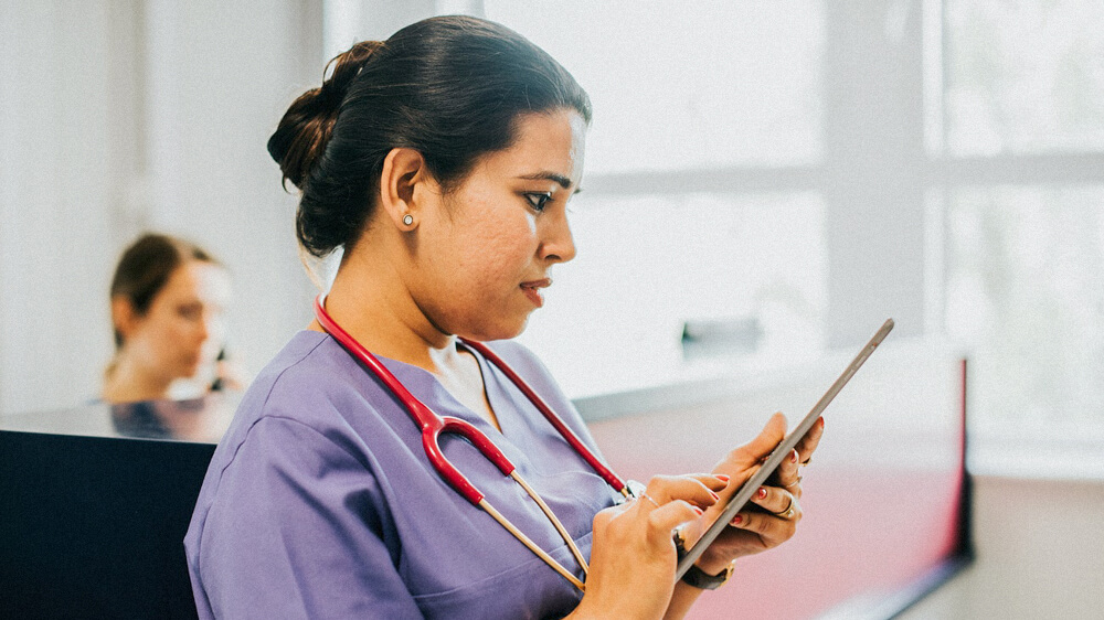 A nurse wearing a stethoscope reads from a tablet.