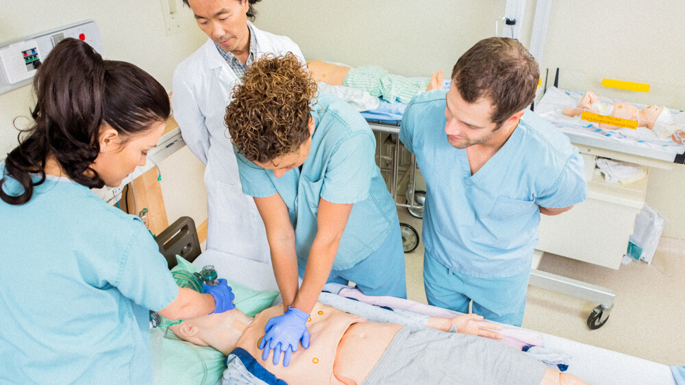 A group of student nurses practice CPR on a dummy while an instructor supervises.