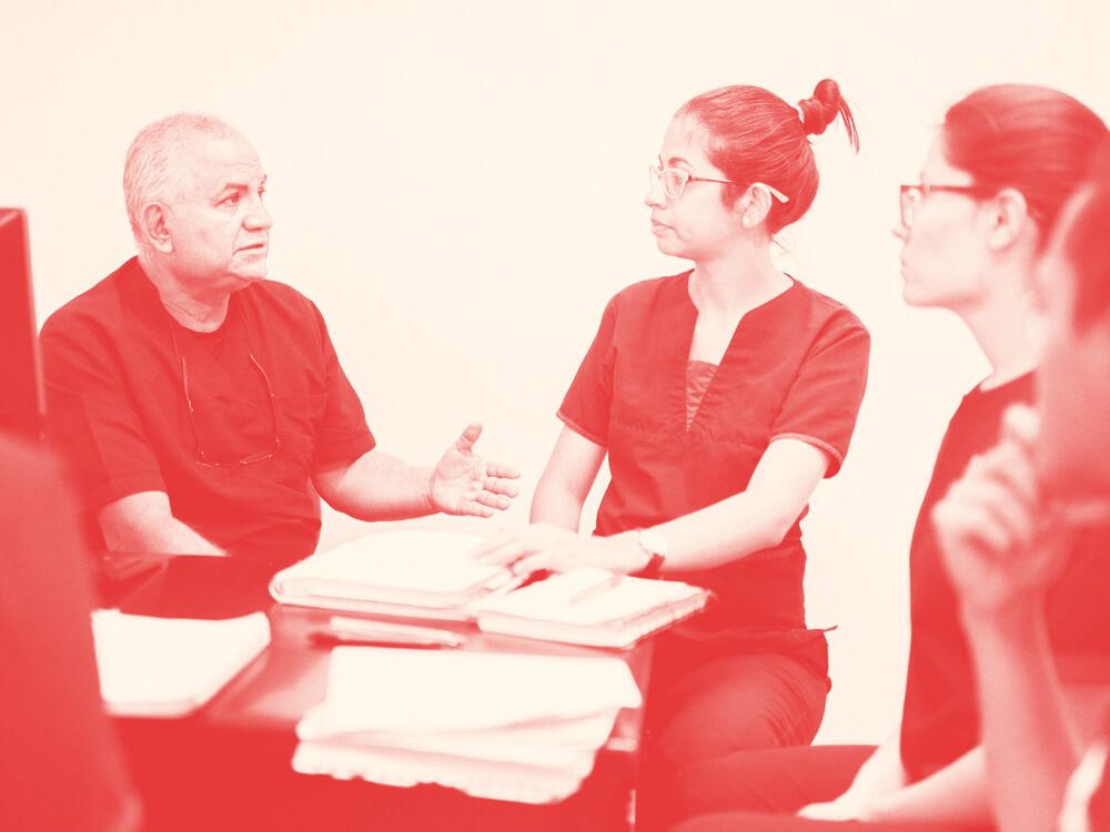 A nurse educator works with a group of nurses around their desk.