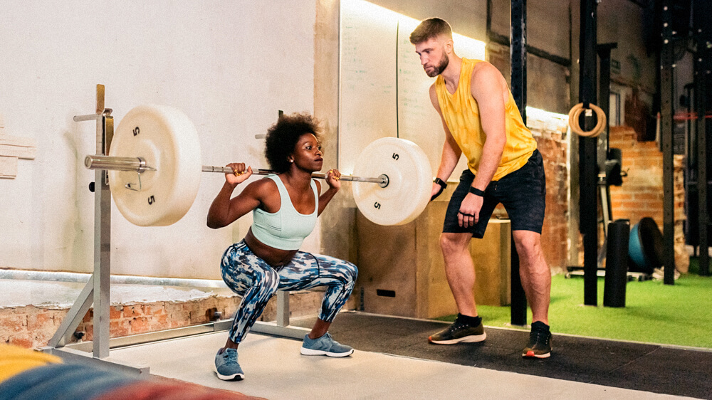 A personal trainer monitors a client performing weighted barbell squats.