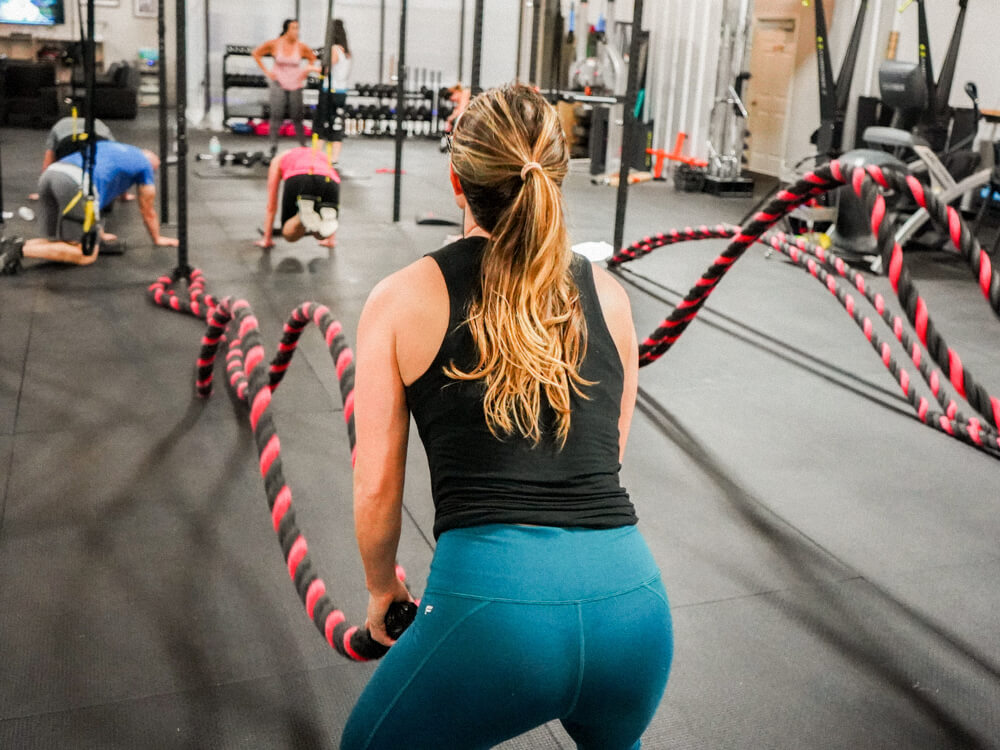 An athlete performs a double wave exercise using battle ropes in a gym.