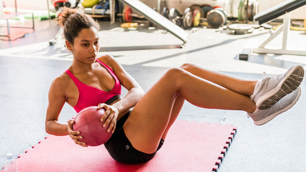 An athlete performs medicine ball side twists in a gym setting.