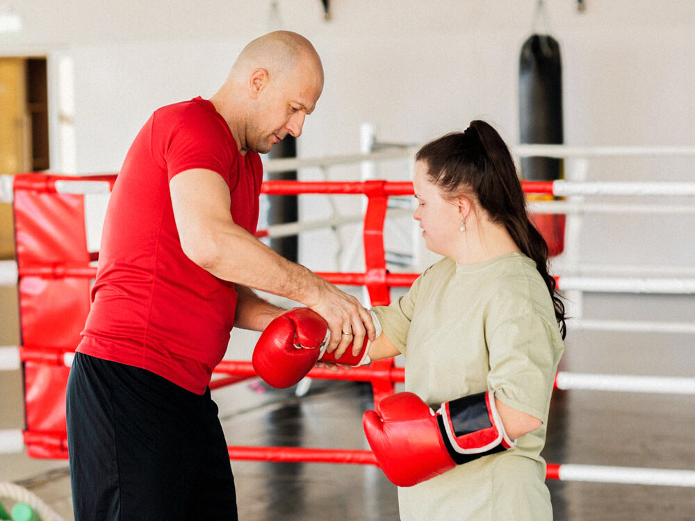 Personal trainer helps client put on boxing gloves in a boxing gym.