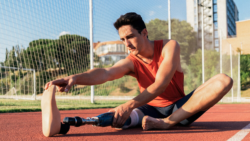 Person with a prosthetic leg stretches on a track.