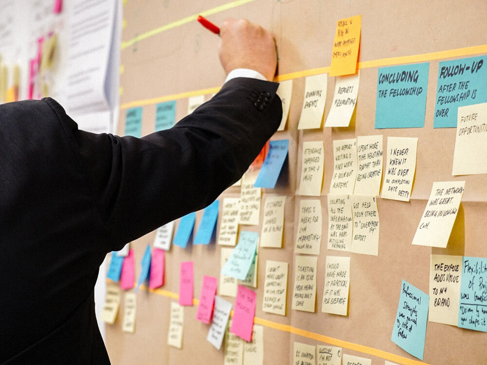 A person adds notes to a wall full of sticky notes.